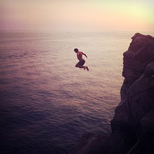 Person jumping from cliff in the summer